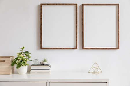 Stylish white home decor of interior with two brown wooden mock up photo frames with books, beautiful plant in stylish pot, gold pyramid and home accessories. Minimalistic scandinavian room.
