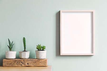 Elegant interieur met mock up frame op de bruine tafel met samenstelling van cactussen en vetplanten op het houten stuk in hipster cement potten. Munt muren. Stijlvol en bloemenconcept huistuin.