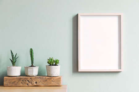 Intérieur de maison élégant avec cadre fictif sur la table marron avec composition de cactus et de succulentes sur la pièce en bois dans des pots de ciment hipster. Murs de menthe. Concept élégant et floral de jardin familial.