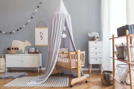 Stylish scandinavian newborn baby room interior with mock up poster , white furnitures, natural toys, hanging grey canopy with stars and teddy bears. Minimalistic and cozy interior of child room. 版權商用圖片 - 120054886