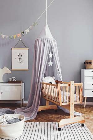 Stilvolles und süßes skandinavisches Dekor des Neugeborenenzimmers mit Mock-up-Poster, weißen Designmöbeln, Naturspielzeug, hängendem grauem Baldachin mit Holzwiege, Kissen, Accessoires und Teddybären. Standard-Bild
