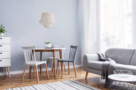 Décor scandinave moderne d'espace ouvert avec mobilier design, table familiale, canapé et plantes Parquet en bois marron et tapis élégant. Appartement agréable et minimaliste. De grandes fenêtres. Lumineux et ensoleillé.