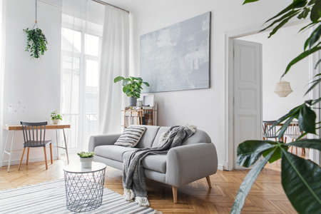 Stylish scandinavian living room with design furniture, plants, bamboo bookstand and wooden desk. Brown wooden parquet. Abstract painting on the white wall. Nice apartment. Modern decor of bright room Zdjęcie Seryjne