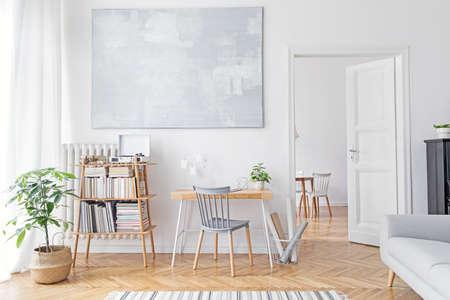 Stilvolle skandinavische Inneneinrichtung mit kreativem Holzschreibtisch, Sofa, Bambus-Buchständer mit Accessoires, Büchern und Pflanzen Freiraum und Wohnzimmer. Braunes Holzparkett und stilvoller Teppich.