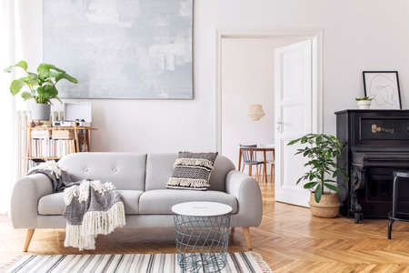 Modern scandianvian decor of living room with design sofa with elegant blanket, coffee table and bookstand on the white wall. Brown wooden parquet. Concept of minimalistic interior with piano. Mock up Zdjęcie Seryjne
