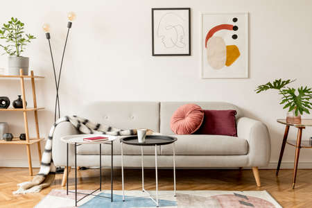 Stylish retro and vintage interior of sitting room with design sofa, tables, lamp, bookstand, blanket and mock up poster frame gallery on the white walls. Interior design with brown wooden parquet .