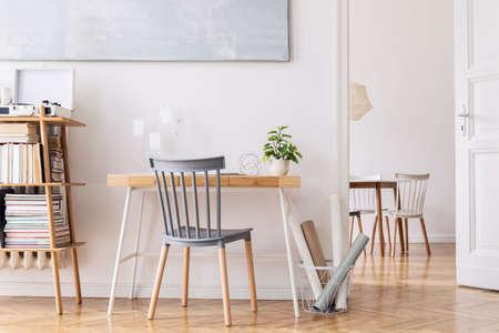Stijlvol scandinavisch interieur van interieur met creatief houten bureau, bamboe boekenstandaard met accessoires, boeken en planten. Open ruimte en woonkamer. Bruin houten parket en stijlvol tapijt.