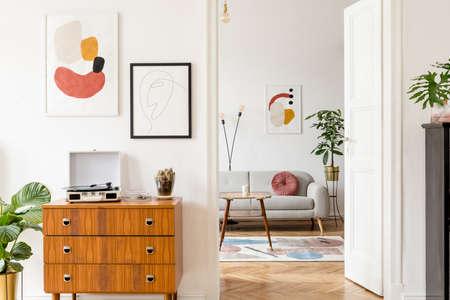 Décor élégant et rétro du salon avec commode design, table basse en vinyle, cactus et cadres d'affiches simulés sur les murs blancs. Chambre élégante avec parquet en bois marron et plantes.