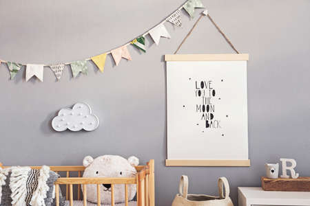 Stylish and cute scandinavian decor of newborn baby room with mock up poster, natural toys, hanging decor flags and cloud, wooden cradle, basket for accessories and teddy bears. Grey walls . Foto de archivo