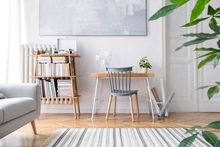 Stylish scandinavian home decor of interior with creative wooden desk, sofa, bamboo bookstand with accessories, books and plants Open space and living room. Brown wooden parquet and stylish carpet.