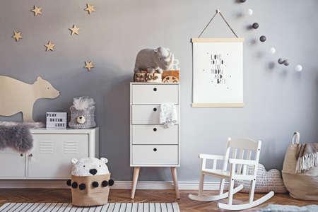 Scandinavische kinderkamer met mock-up posterframe op de grijze muur, witte meubels, natuurlijke teddybeer en speelgoed. Leuk modern interieur van speelkamer met witte muren, babyaccessoires en speelgoed.
