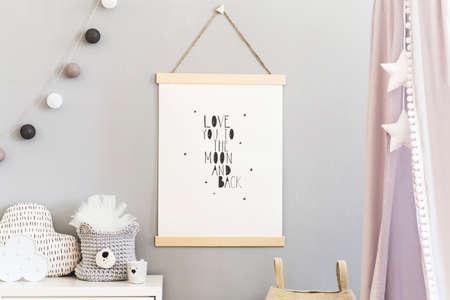 Intérieur de pépinière scandinave élégant avec affiche de maquette suspendue, auvent gris avec étoiles et étagère blanche avec oreiller nuage, panier naturel et accessoires pour enfants. Mur de fond gris.