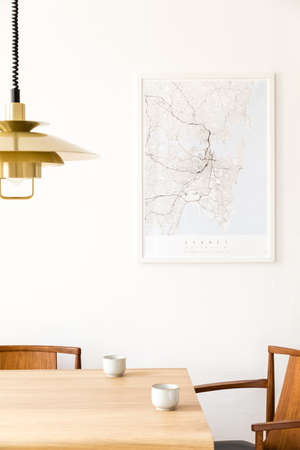Stylish and modern dining room interior with mock up poster map, sharing table design chairs, gold pedant lamp and cups of coffee. White walls, wooden parquet. Minimalistic and eclectic decor.