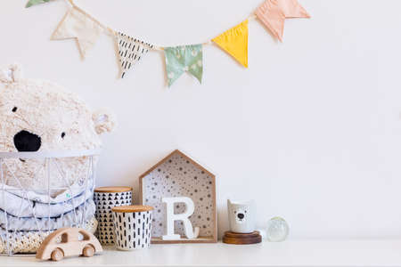 Stylish scandinavian nursery interior with white teddy bear, wooden toys,boxes, accessories and child's cup. Hanging cotton flags and basket on the white background wall. Cozy and sunny childroom.