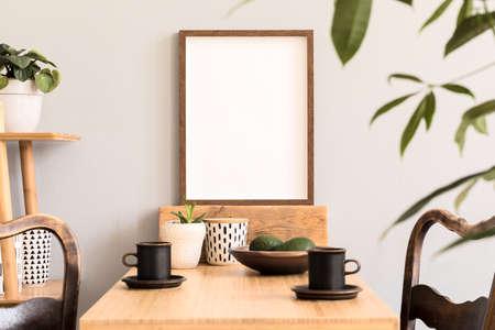 Intérieur élégant et ensoleillé de l'espace cuisine avec table en bois avec cadre photo marron, chaises design et étagère en bambou. Décor de chambre scandinave avec accessoires de cuisine et belles plantes.