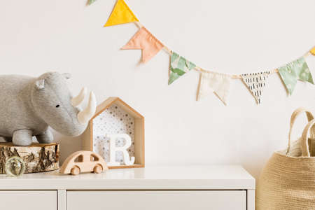 The modern scandinavian newborn baby room with plush rhino, design toys and box on the white shelf. Hanging cotton flags on the white background wall. Stylish and cozy interior. Copy space. Real photo