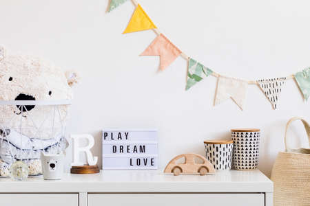 Stylish scandinavian child room home decor. Cute modern interior of playroom with boxes, teddy bear, toys. wooden accessories and colorful flags on the white shelf. Real photo.
