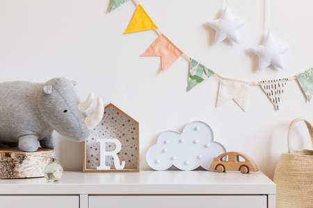 The modern scandinavian newborn baby room with plush rhino, design boxes, wooden toys, cloud and natural basket. Hanging cotton flags and stars on the white background wall. Stylish and cozy interior. Foto de archivo