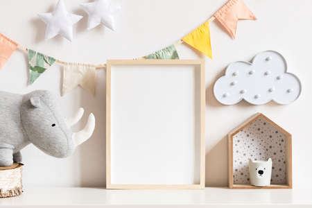 The modern scandinavian newborn baby room with mock up photo frame, wooden toy, plush rhino and clouds. Hanging cotton flags, white stars and cloud. Minimalistic and cozy decor of childroom. 版權商用圖片