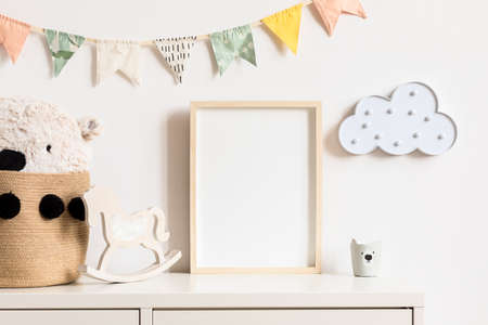 Stylish and modern scandinavian childroom interior with mock up photo or poster frame on the white shelf. Toys, teddy bear in basket, rocking horse and hanging cotton colorful flags and cloud.
