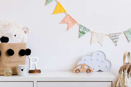 Stylish and modern scandinavian child room with hanging cotton colorful flags on the white wall, boxes, teddy bear in natural basket, toys. wooden accessories and cloud. Real photo. Stock Photo