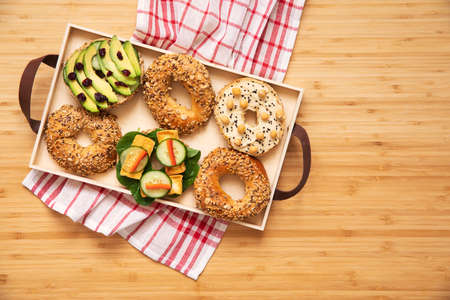 Stylish and tasty composition of vegan bagels sandwiches on the salver with vegetables, herbs, paste, seeds, hummus and lettuce on the brown wooden table. Fresh and healthy breakfast.