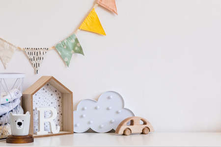 Stylish and cozy childroom with wooden toys, cloud and hanging cotton flags. Modern scanidnavian interior with white background wall. Copy space for inscription or product. Real phote. Template.