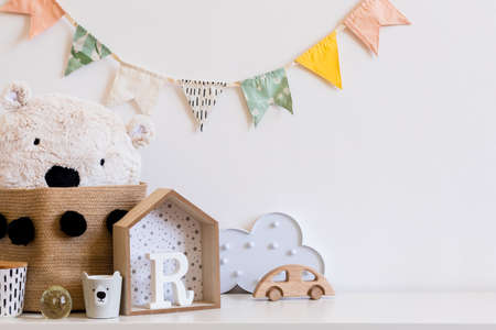 Stylish scandinavian child room with hanging cotton colorful flags on the white wall, boxes, teddy bear in natural basket, toys. wooden accessories and cloud. Real photo. Copy space for inscription.