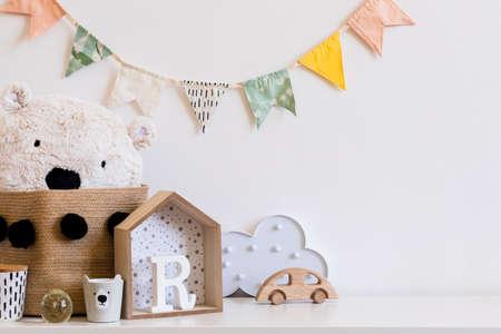 Stijlvolle scandinavische kinderkamer met hangende katoenen kleurrijke vlaggen aan de witte muur, dozen, teddybeer in natuurlijke mand, speelgoed. houten accessoires en wolk. Echte foto. Kopieer ruimte voor inscriptie.