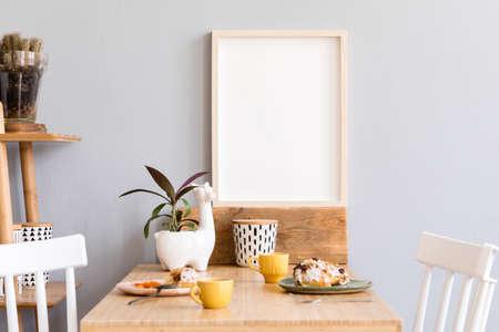 Stijlvol en zonnig interieur van keukenruimte met kleine houten tafel met mock-up fotolijst, designbekers en smakelijk dessert. Scandinavische kamerinrichting met keukenaccessoires, cactussen en planten.