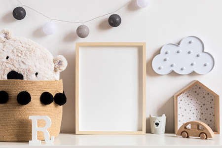 Stylish and modern scandinavian newborn baby interior with mock up photo or poster frame on the white shelf. Wooden toys, teddy bear, cup and hanging cotton lamps and star. Template. Blank. Real photo Stockfoto