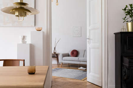 Modernes Scandi-Interieur des Wohnzimmers mit Design-Holztisch, Stühlen, Sofa und weißen Ständern mit stilvollen Accessoires. Abstrakte Gemälde an der Wand. Elegante Wohnkultur. Mock-up-Posterrahmen.