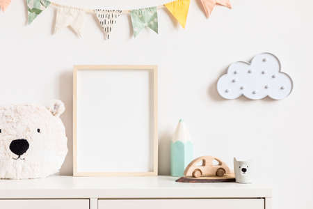 Stylish and modern scandinavian newborn baby interior with mock up photo or poster frame on the white shelf. Toys, teddy bear, wooden car and hanging cotton colorful flags and star. Template. Blank. Stock Photo
