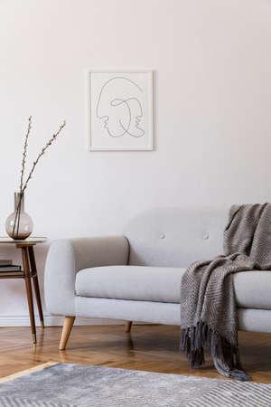 Intérieur scandi élégant de l'espace domestique avec canapé gris design et petite table rétro. Salon avec accessoires design et cadre d'affiche maquette. Décor élégant. Parquet en bois marron avec moquette moderne.