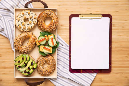 Stylish and tasty composition of vegan and vegetarian breakfast. Planning your healthy diet. Organic vegetables and sandwiches on the wooden table. Mock up menu concept. Fresh and healthy meal.