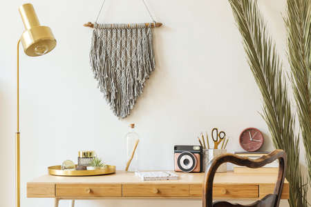 Stylish scanidnavian interior with wooden desk, grey macrame, design accessories, photo camera, gold lamp and wooden ladder on the white wall. Piece of design woman's room. Creative desk of home decor