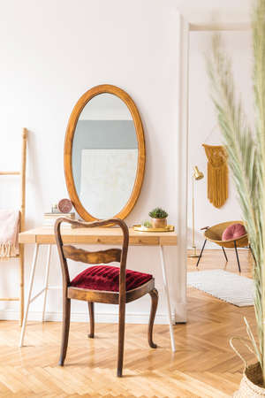 Stylish and elegant home interior with wooden desk, retro chair, design accessories, gold lamp and dressing table with mirror. Piece of design woman's room. Open space. Minimalistic and warm space.