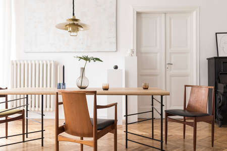 Eklektisches und elegantes Esszimmer mit Design-Sharing-Tisch, Stühlen, goldener Pendelleuchte, abstrakten Gemälden, Klavier und stilvollen Accessoires. Minimalistische Einrichtung. Braunes Holzparkett. Echtes Foto.