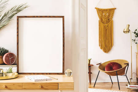 Elegant scanidnavian interior of apartment with mock up poster frame, gold armchair, design accessories and furnitures, big yellow macrame on the white wall. Cozy design home decor of sitting room.