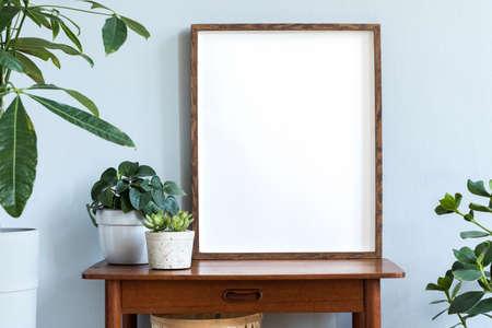 Intérieur scandinave élégant avec table rétro design, cadre photo marron et belles plantes dans des pots en ciment. Décoration d'intérieur moderne. Mur de fond gris. Concept minimaliste. Modèle
