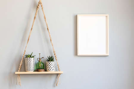 Stylish and minimalistic scandinavian interior with mock up poster frame and hanging wooden shelf with beautiful succulents in hipster pots and green sprinkler. Modern home decor. Template.