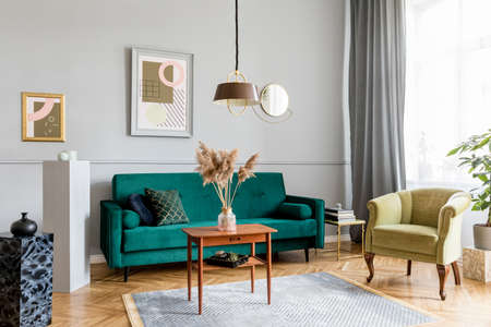 Stylish and elegant living room of apartment interior with green velvet armchair and sofa, brwon table, plant, design lamp and chic accessories. Abstract paintings on the gray wall. Luxury home decor. Stockfoto