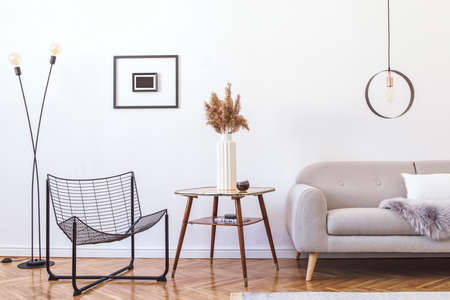 Stylish minimalistic living room with design grey sofa, black armchair, geometric lamp, retro table and elegant accessories Mock up posters frame on the white walls. Minimalistic home decor.
