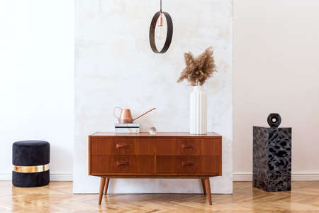 Stylish and eclectic interior of living room with design retro cabinet, round pendant lamp, marble pedestals and elegant accessories. Abstract background wall. Minimalistic home decor. Copy space.