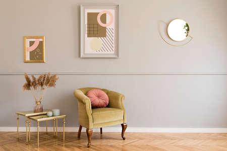 Sala de estar elegante y de lujo del interior del apartamento con elegante sillón verde, mesas retro, lámparas de diseño, accesorios elegantes y espejo dorado. Simulacros de marcos en la moldura de pared gris. Decoración del hogar.