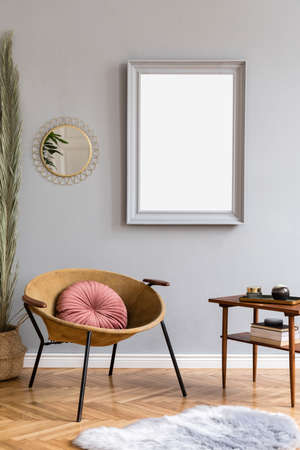 Stylish and luxury interior of with design honey yellow armchair, gray mock up frame, gold mirror, palm leaves and pillow Retro small table with elegant accessories. Modern home decor of living room.