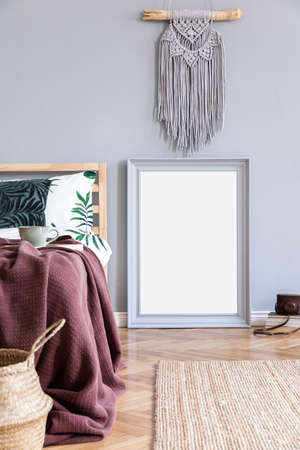 Stylish and luxury interior of bedroom with gray mock up frame, macrame and elegant accessories. Beautiful floral bed sheets, blankets and pillows. Modern home decor. Brown wooden parquet.