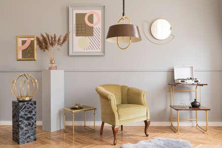 Stijlvolle en luxe woonkamer van appartement interieur met elegante groene fauteuil, retro tafels, marmeren stands, design lampen, chique accessoires en gouden spiegel. Mock-up frames op de grijze muur. Stockfoto