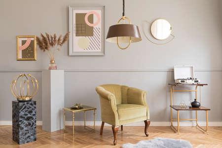 Stylish and luxury living room of apartment interior with elegant green armchair, retro tables, marble stands, design lamps, chic accessories and gold mirror. Mock up frames on the molding gray wall. Zdjęcie Seryjne