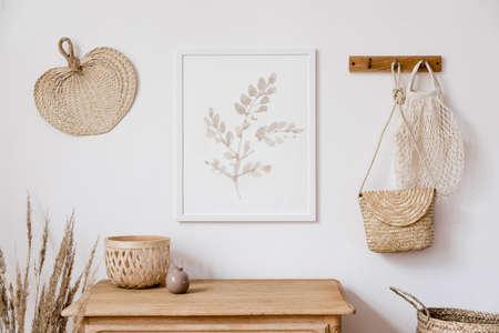 Elegante interior coreano de sala de estar con marco de póster simulado marrón, accesorios elegantes, flores en jarrón, estante de madera y hojas colgantes de ratán, bolsos. Concepto minimalista de decoración del hogar. Plantilla.